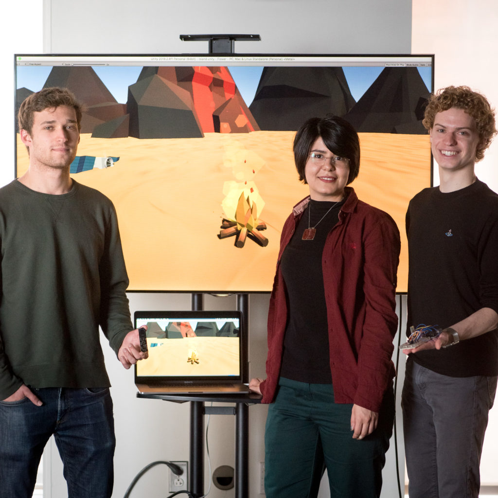 Three people standing in front of a monitor holding an electronic interface device for immersive experiences.