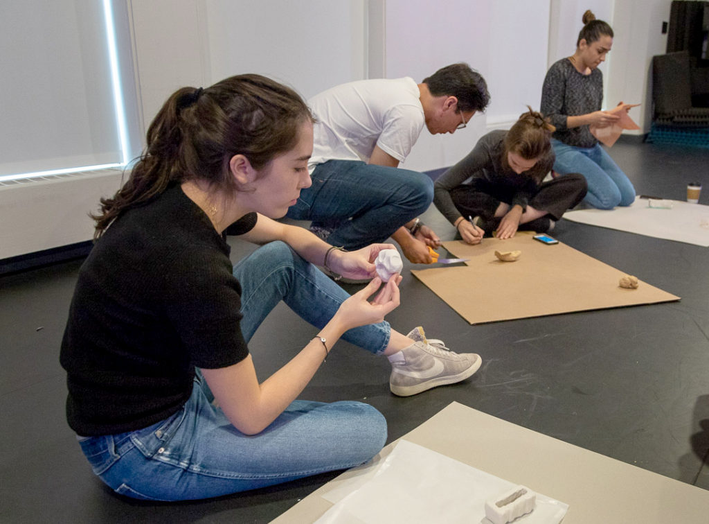 A girl and three other students working on something using clay.